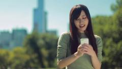 Young Asian Woman texting cellphone in a park Stock Footage