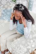 Woman with headache sitting on sofa Stock Photos