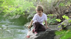 Little boy playing with wooden boat by a river on spring or autumn day Stock Footage