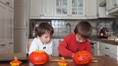 Two kids, cutting pumpkins for Halloween Stock Footage