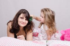 Girl combing her hair with enthusiasm mum Stock Photos