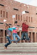 Happy students jumping in the air holding exam Stock Photos