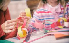 Christmas: parent and child work on paper chain garland Stock Photos