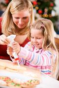 Christmas: girl uses icing to decorate christmas cookies Stock Photos