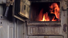 Zoom out of burning wood in stove, woman sit in chair and read Stock Footage