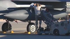 Ground crew members load munitions onto an F-15E Strike Eagle aircraft Stock Footage