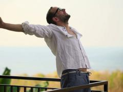 Young man stretching, yawning on terrace in the morning NTSC Stock Footage