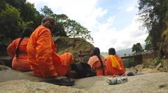 Religious group sitting on rocks at Ravana waterfalls. Stock Footage