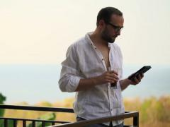 Young man reading e-book on e-book reader on terrace NTSC Stock Footage