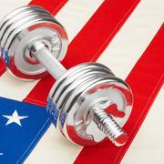 Stock Photo of metal dumbbells over us flag as symbol of healthy nation - studio shot