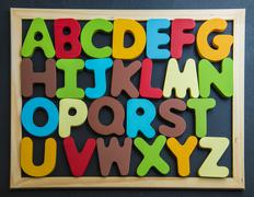 colorful wooden alphabet on black board - stock photo