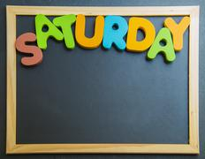 colorful wooden word saturday on black board - stock photo