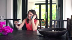 Young woman talking on cellphone and drinking wine by dining table HD Stock Footage