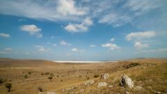 Clouds float over the fields and dry lake. timelapse. Stock Footage