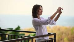 Woman taking photo of beautiful view from terrace HD Stock Footage