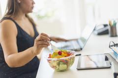 Woman working in home office and eating salad Stock Photos