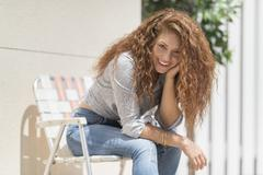 Portrait of woman sitting in deck chair outdoors Stock Photos