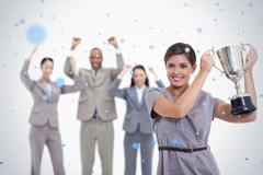 Woman holding up a cup with enthusiastic coworkers Stock Photos