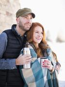 Mid adult couple having drink from vacuum flask, looking away - stock photo
