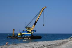 the floating crane on the seacoast - stock photo
