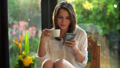 Young woman texting on smartphone, drinking coffee at home HD Stock Footage