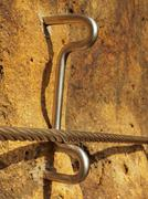 Detail of rope end anchored into sandstone rock. Iron twisted fixed  rope Stock Photos