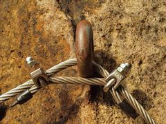 Detail of rope end anchored into sandstone rock. Iron twisted fixed rope fixed Stock Photos