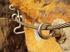 Detail of rope end anchored into sandstone rock. Iron twisted rope Stock Photos