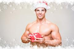 Composite image of shirtless macho man in santa hat holding gift - stock illustration