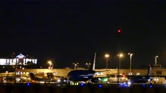 4K UHD - 3 planes taxiing at night with airport lights in background Stock Footage