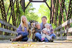 portrait of happy family and dog sitting on bridge in autumn woods - stock photo