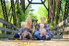family of four people and dog sitting on bridge in autumn - stock photo