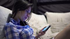 Young woman watching movie on smartphone on bed at night HD - stock footage