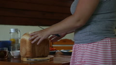 Woman cuts off white bread crust Stock Footage