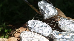 Baked potatoes on the grill in foil at the stake Stock Footage