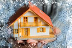 hands showing a miniature model home against snow - stock photo