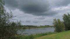 Dark clouds above river river IJssel + pan riverbed and dike CORTENOEVER Stock Footage