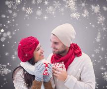 composite image of winter couple holding mugs against grey vignette - stock photo