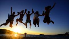 Silhouette of friends jumping on beach during sunset time, slow motion Stock Footage