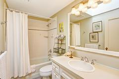 white refreshing bathroom with cabinet and mirror - stock photo