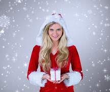 pretty girl in santa outfit holding gift against grey vignette - stock photo