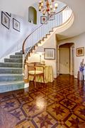 luxury foyer with designed hardwood floor and spiral staircase - stock photo