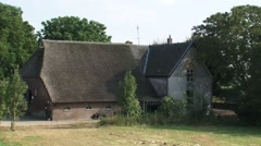 Old thatched farmhouse with housebarn in floodplains river IJssel t Stock Footage