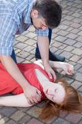 man checking up consciousness of young girl - stock photo