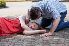 man checking pulse of fainted girl - stock photo