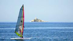 Young man surfing the wind at ocean horizon and island lighthouse at backgrou Stock Footage