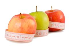 Pink measuring tape and three apples Stock Photos
