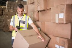 Worker scanning package in warehouse - stock photo