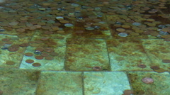 Coins in the clear water - stock footage