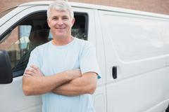Smiling man in front of delivery van - stock photo